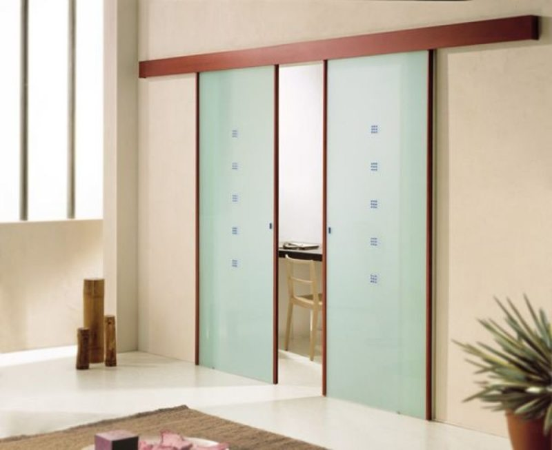 Светлое оформление гостиной небольшого размера с дверями из матового стекла