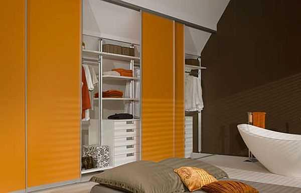 Вариант гардеробной в мансарде: под нее занята боковая часть с невысоким потолком. Двери во всю ширину — проще добираться к вещам