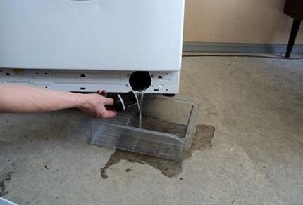 Пробка сливного фильтра стиральной машины, откручивается против часовой стрелки, а если не получается вытащить ее руками, можно использовать плоскогубцы