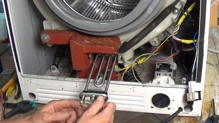 Если через полученное отверстие в месте крепления ТЭНа стиральной машины ничего не видно, попробуйте покрутить барабан и застрявшие сверху предметы опустятся вниз