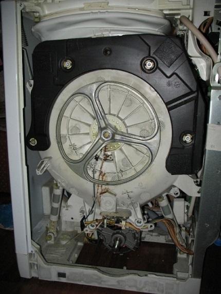При разборке стиральной машинке не укладывайте её на бок, только наклоняйте: в ней всегда есть остатки воды, которые могут пролиться на детали механизма