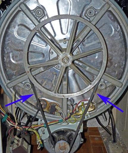 На рисунке стрелочки указывают на ремень. Натяжка клинового ремня стиральной машины должна быть очень плотной: если сильно нажать в середине, прогиб до 5 мм считается нормальным