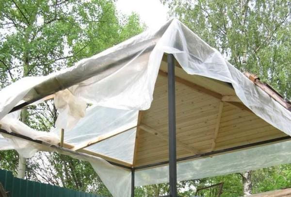 Чтобы доска (внизу получается длина более 3 метров) не прогибалась, примерно от середины прибиты укосины (пленка — от дождя, хоть древесина и обработана)