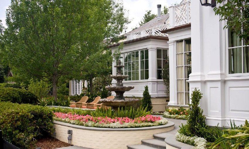 Цветочная клумба, огражденная кирпичной стеной, станет красивым дополнением двора в частном доме