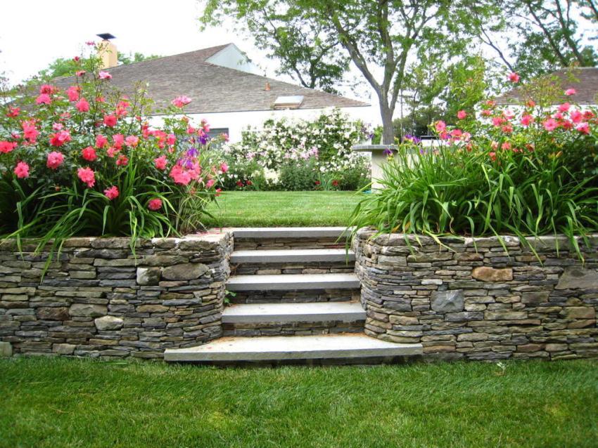 Две каменные клумбы с цветами обрамляют садовые ступеньки