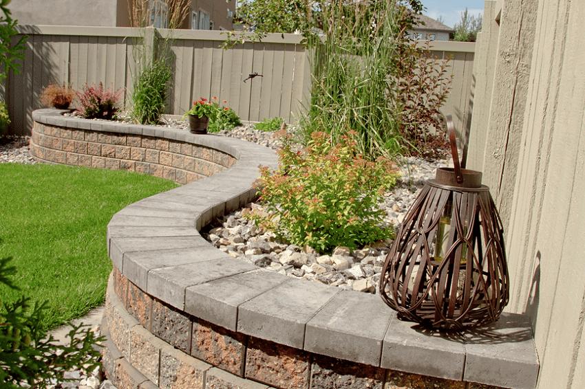 Волнообразная каменная конструкция с зелеными насаждениями